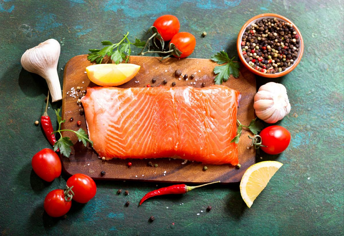 fresh salmon with vegetables on wooden board