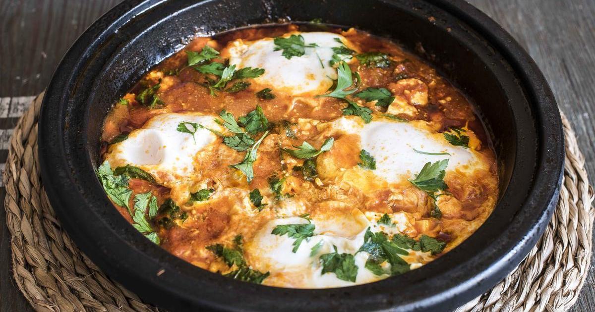 Huevos al plato con feta, salsa de tomate y cilantro