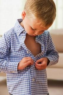 West New York, New Jersey, USA --- Caucasian boy buttoning his shirt --- Image by © KidStock/Blend Images/Corbis