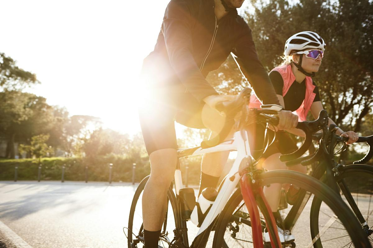 Cropped view of unrecognizable male cyclist having evening ride at sunset with his attractive blonde girlfriend who is having happy and carefree look, enjoying warm weather and good cycling