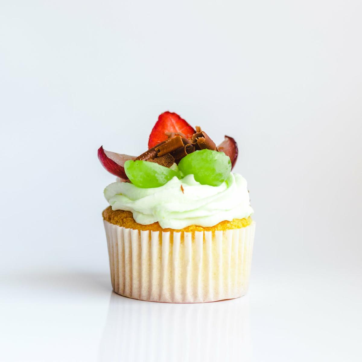 white and yellow cupcake with fruit toppings
