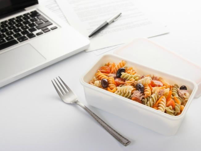 Eating a pasta salad with vegetables and tuna in the office