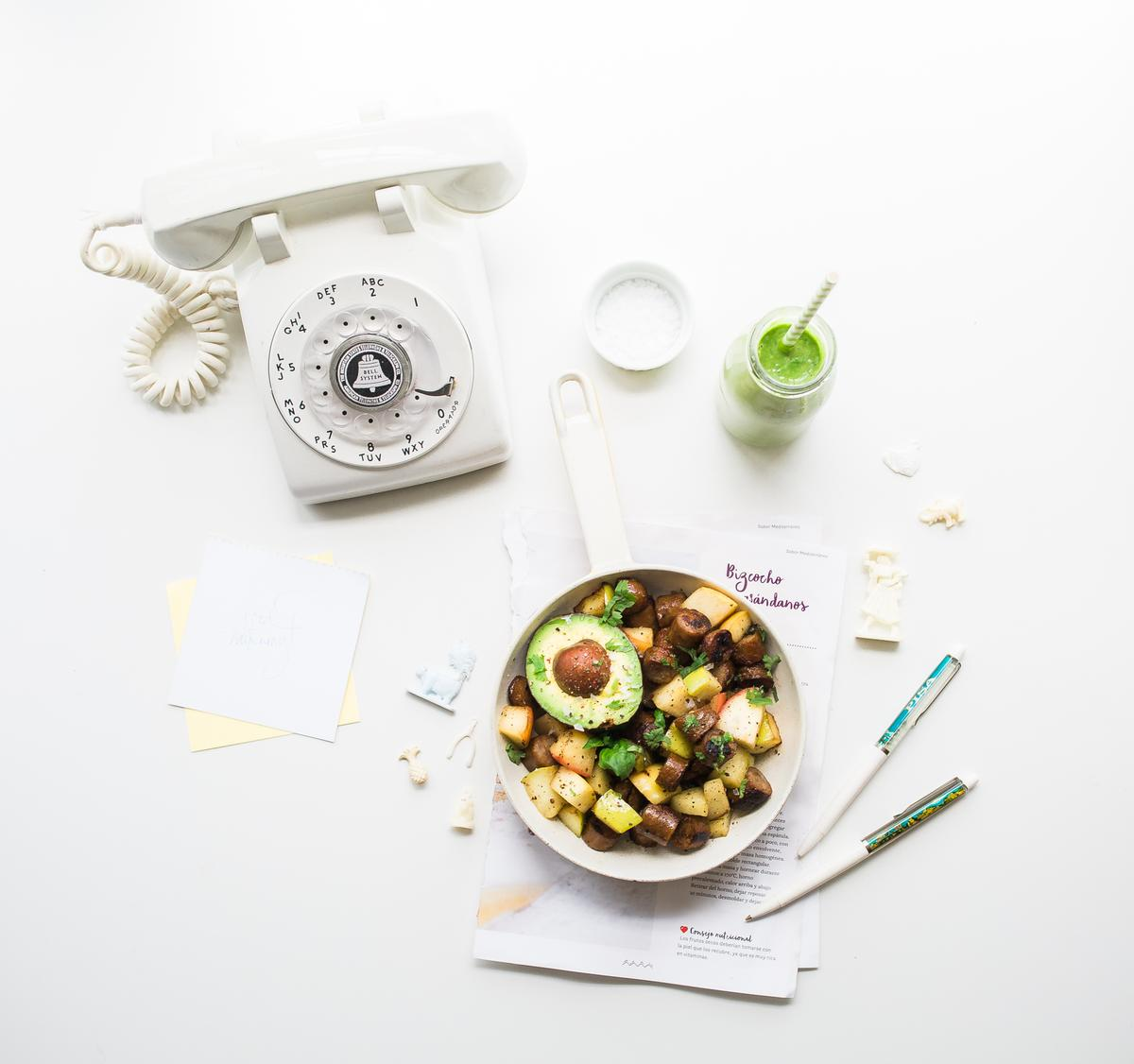 sliced avocado fruit inside bowl near rotary phone beside jar