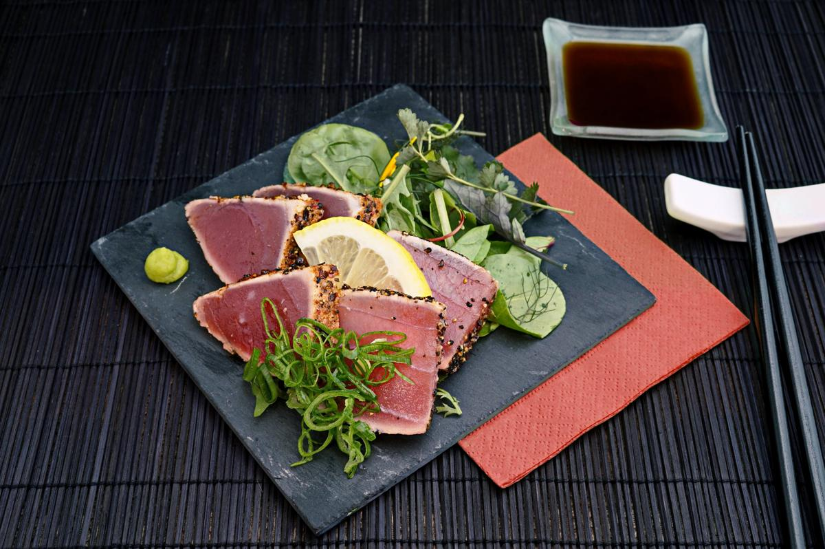 tuna with lemon and greens salad on black plate
